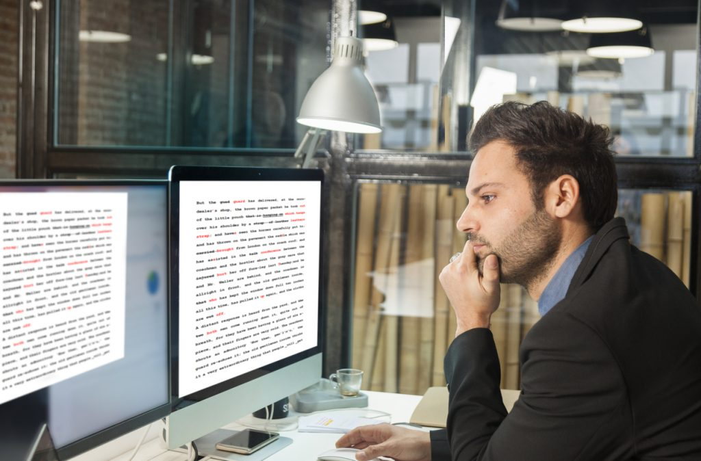 Man proofreading his document before printing to ensure he doesn't waste paper.