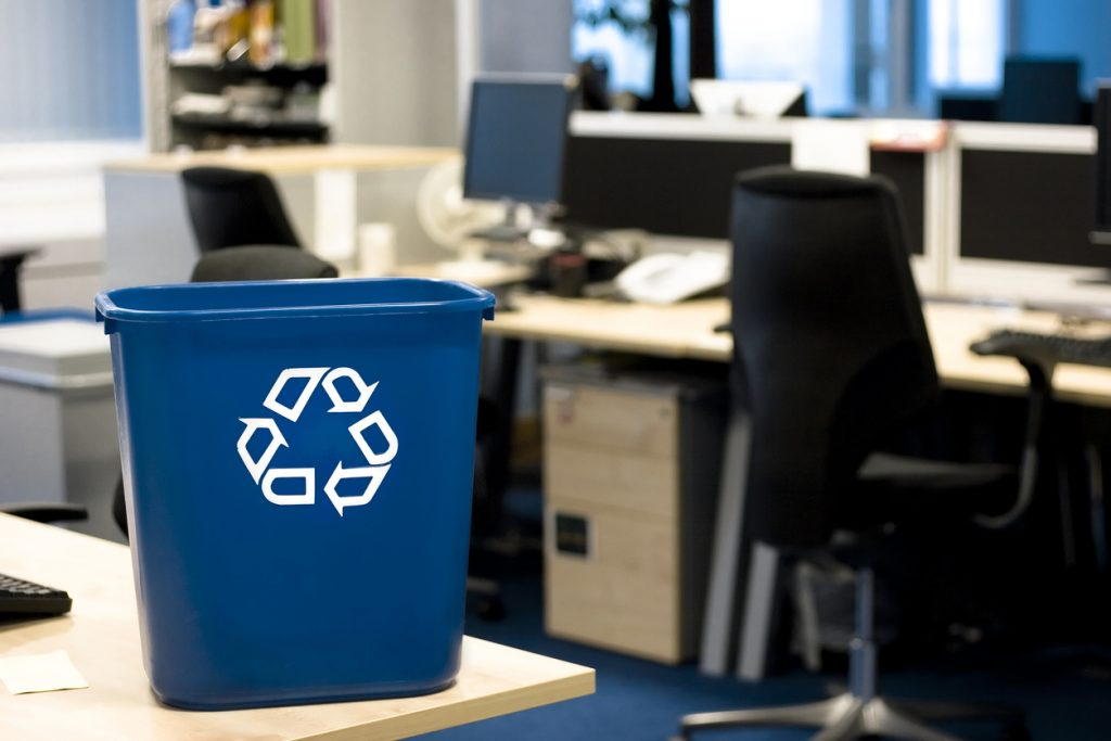 Blue recycling bin in the office helping to remind employees to recycle their paper.