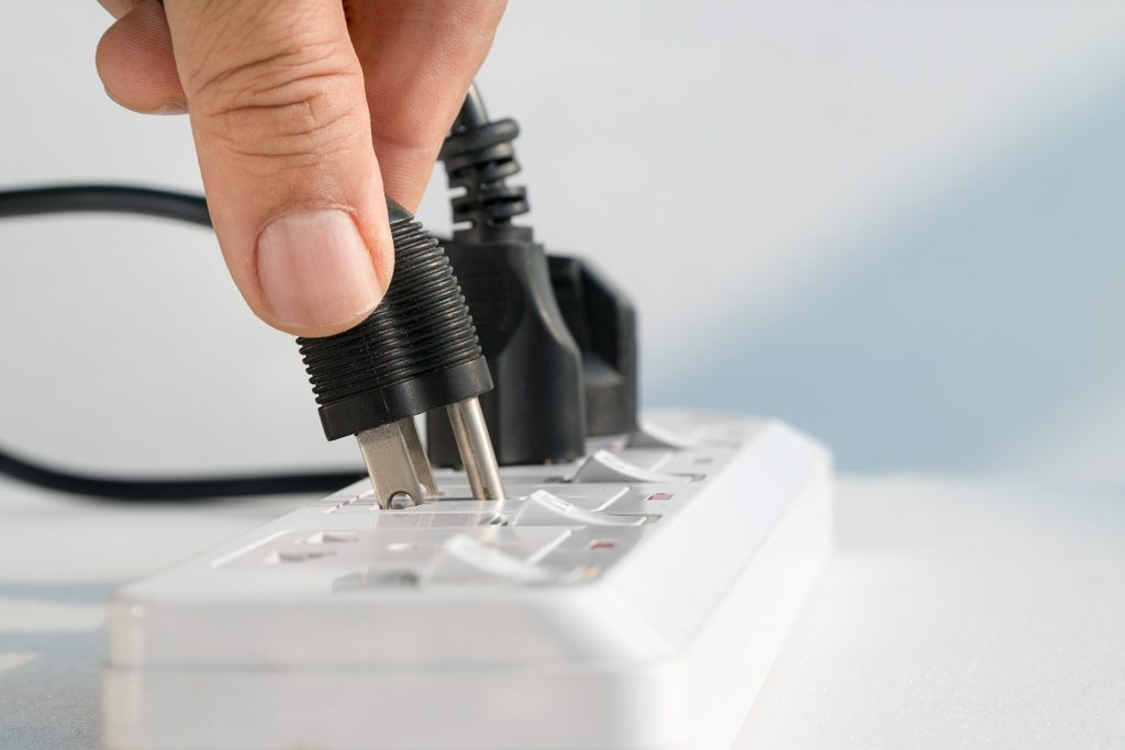 Close up of hand plugging printer cord into a power bar.