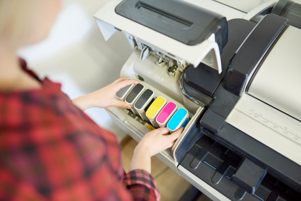 Woman looking at printer ink cartridges.