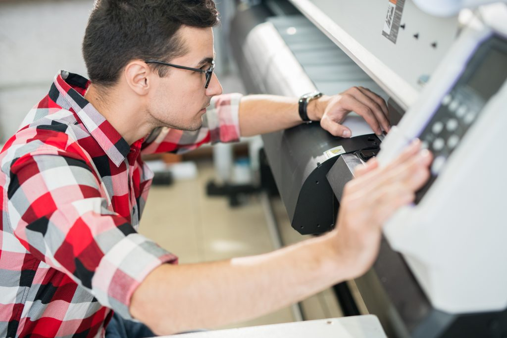 Man using a wide format printer.